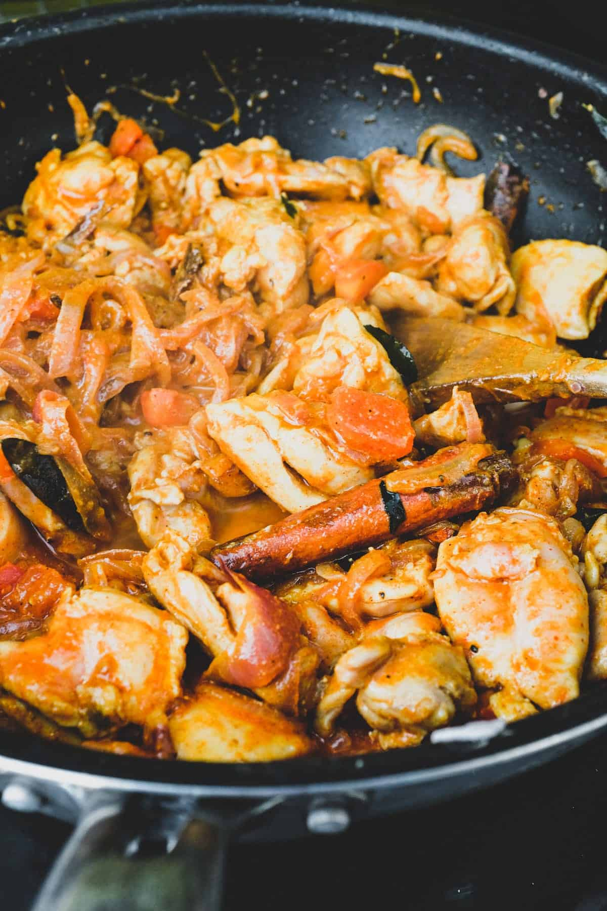Chicken cooked with vinegar. spices, garlic and tomato.