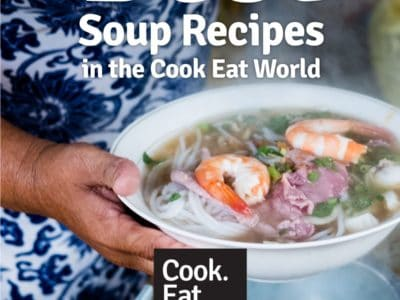 A close up photograph of a Vietnamese woman holding a bowl of Pho Soup with shrimp, beef and noodles - leading to a post about the best soup recipes from cookeatworld.com