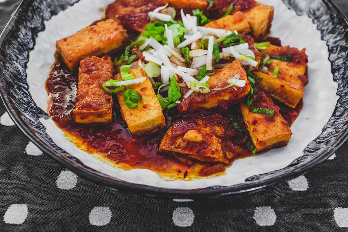 Fried tofu is lightly braised in Korean chilli (gochugaru) and topped with radish and spring onion