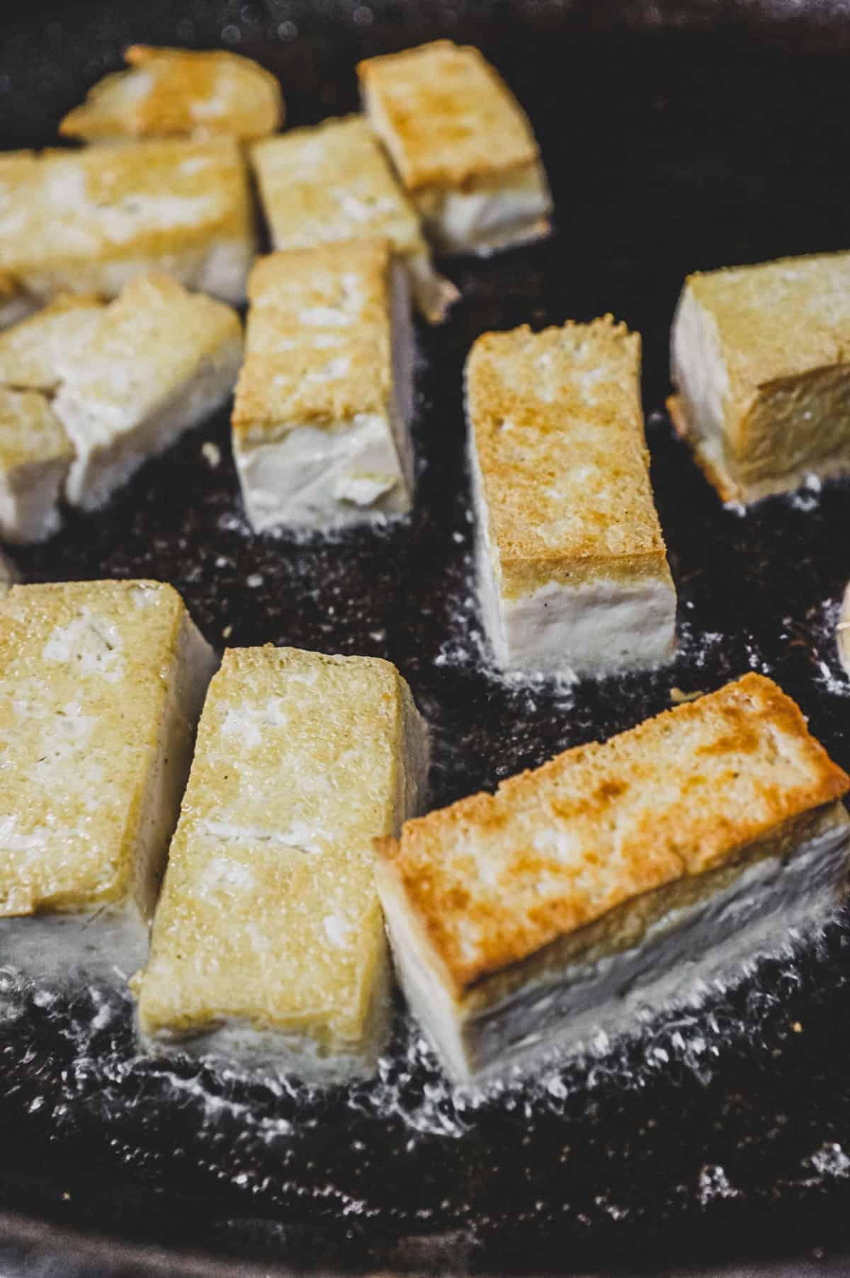 Tofu being fried in canola oil until crisp
