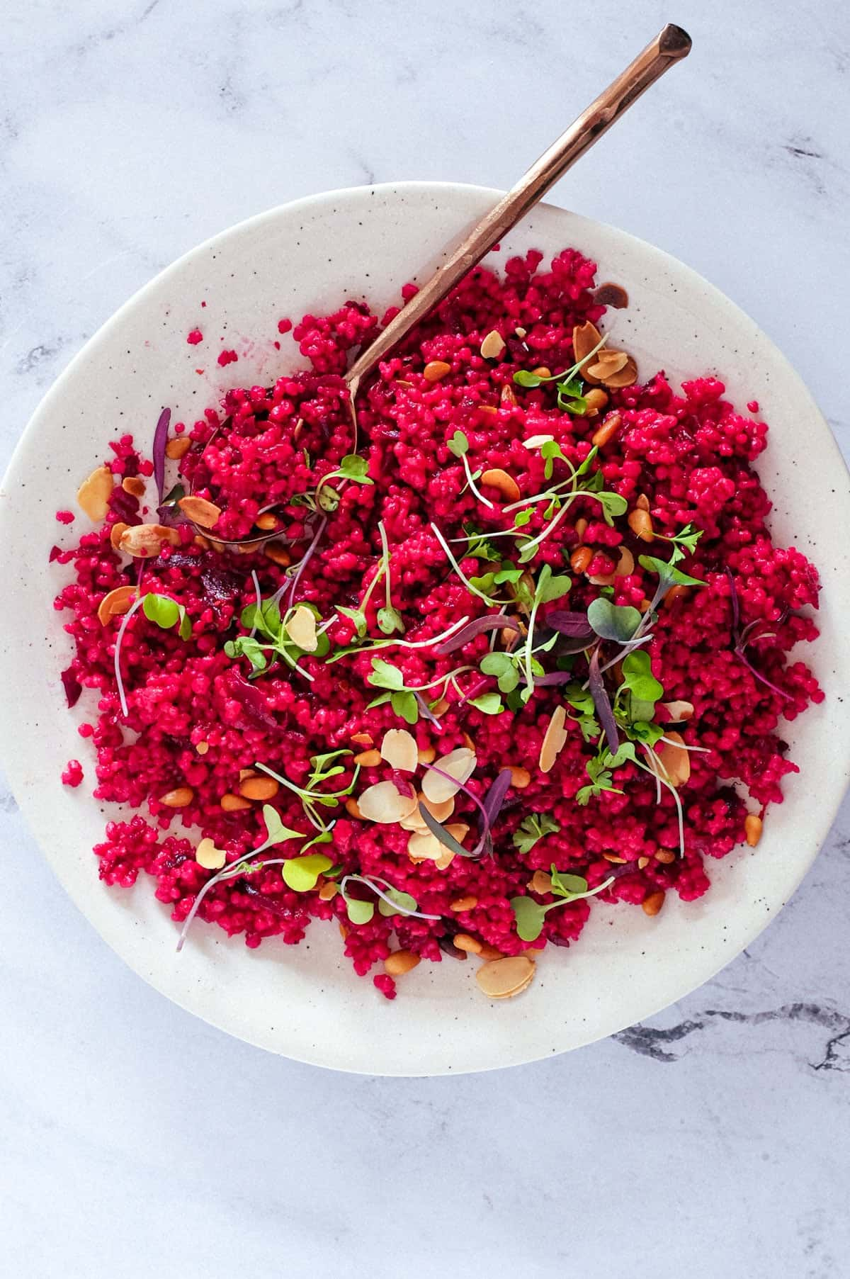 Israeli Couscous with Beetroot on a plate, scattered with micro greens and nuts.