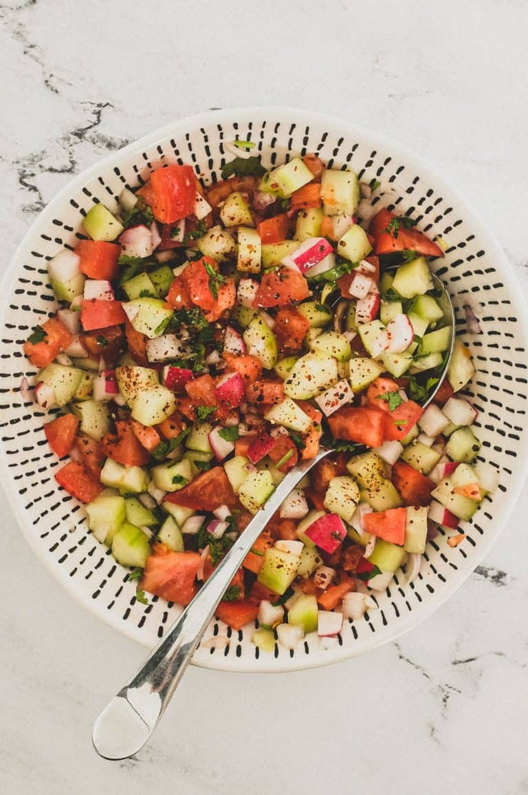 Cucumber, tomato & red onion are combined with a little cilantro and lime juice and served in a bowl as a chopped salad for Indian food.