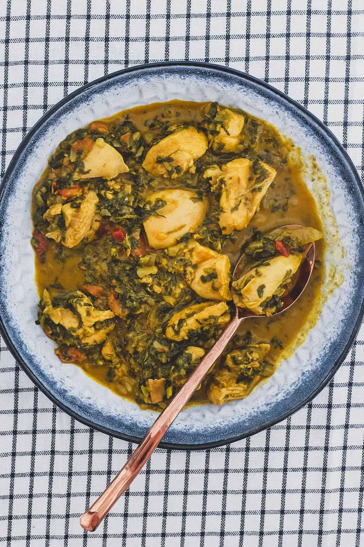 A bowl of chicken curry cooked with fenugreek leaves with a serving spoon