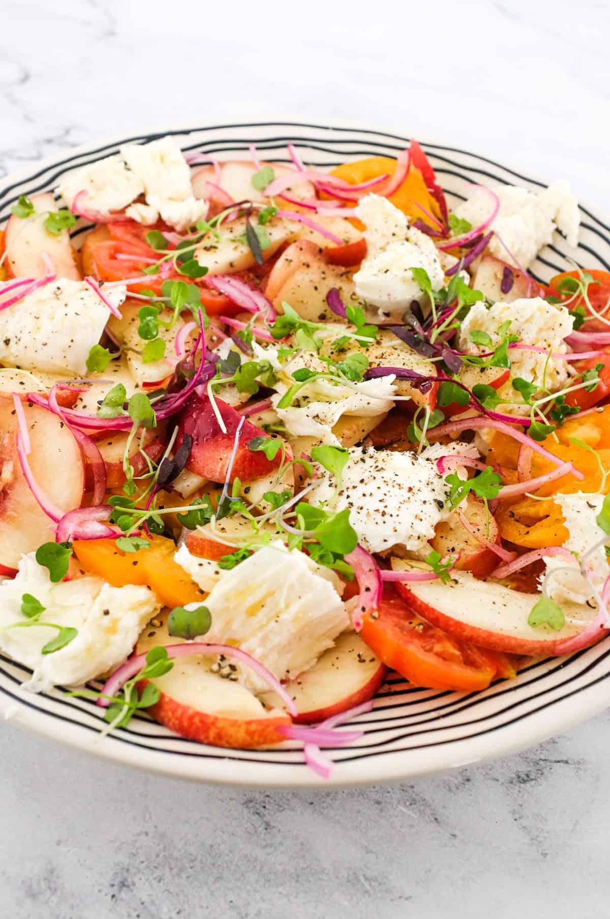 A salad of peaches, burrata cheese, tomato, red onion and micro greens sits on a marble countertop