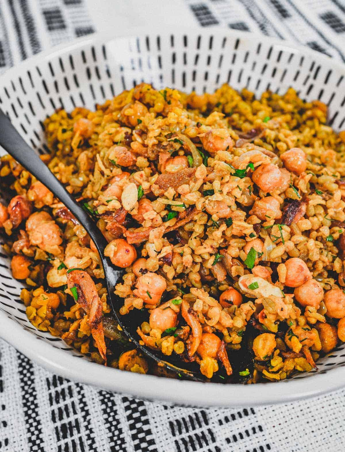 Freekeh cooked with onion and chickpeas in a large serving bowl