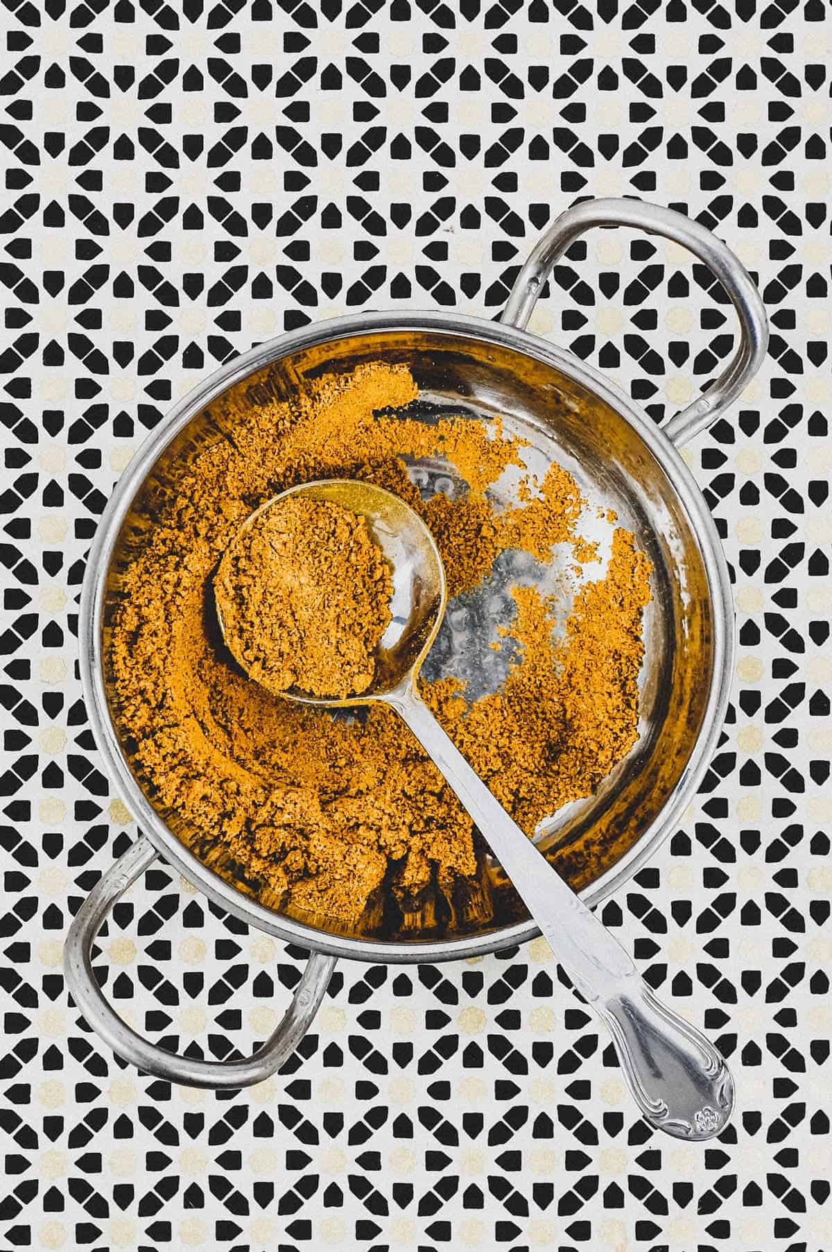 Ground spices combined with turmeric form a yellow spice powder called Hawaij, shown here in a silver bowl with spoon on an Arabic patterned background.